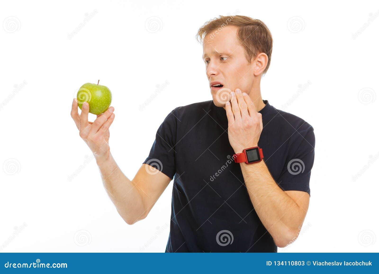 Trauriger freudloser Mann, der den grünen Apfel betrachtet