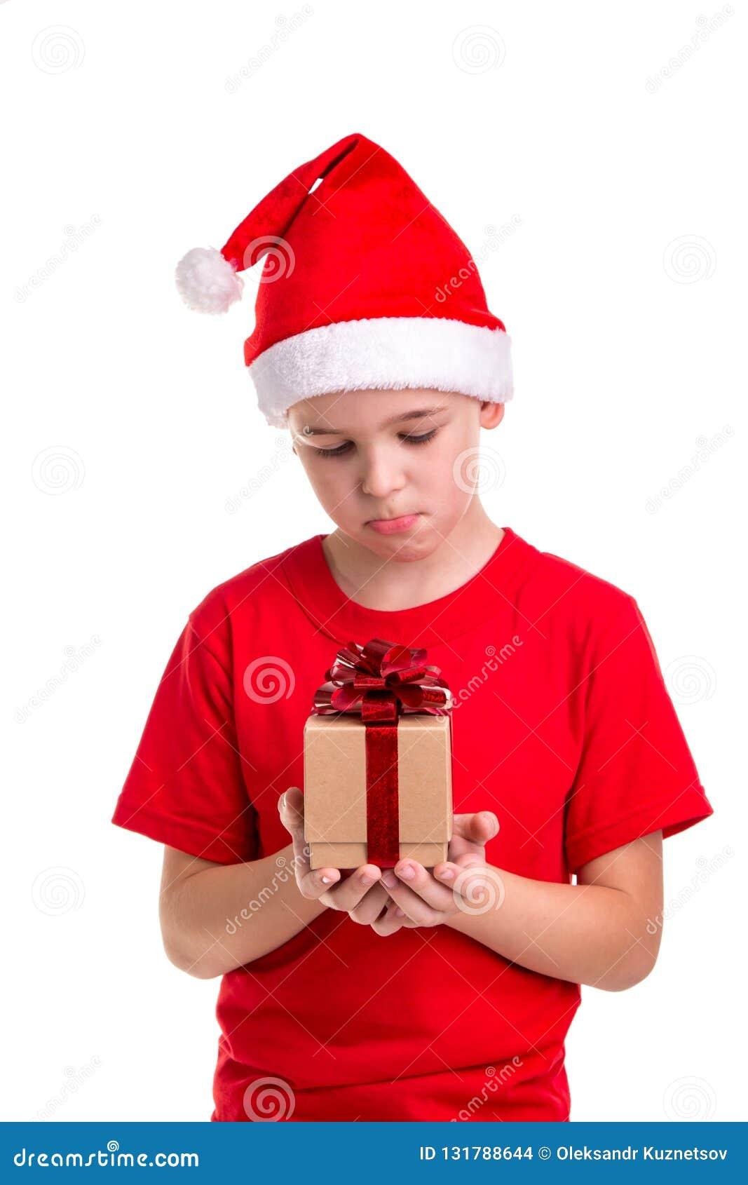 Trauriger Junge, Sankt-Hut auf seinem Kopf, mit der kleinen Geschenkbox in den Händen Konzept: Weihnachten oder guten Rutsch ins