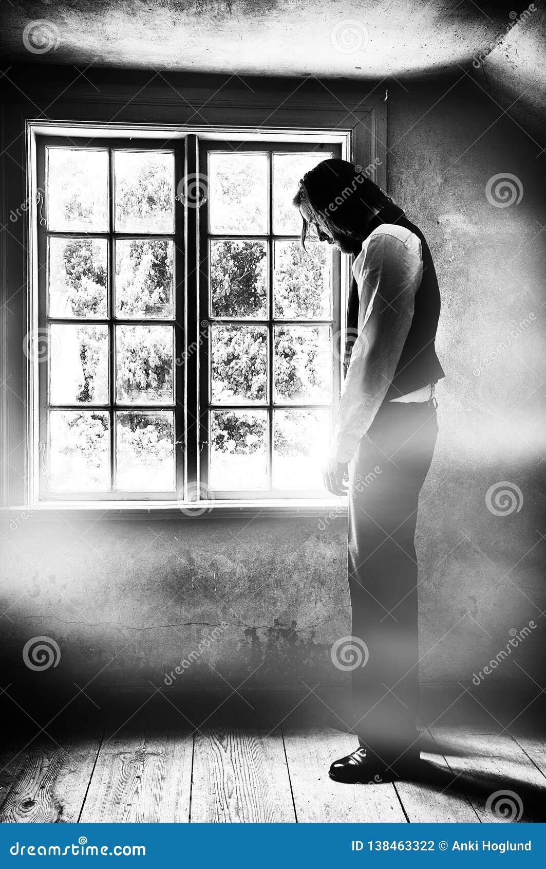 Trauriger junger Mann vor Fenster