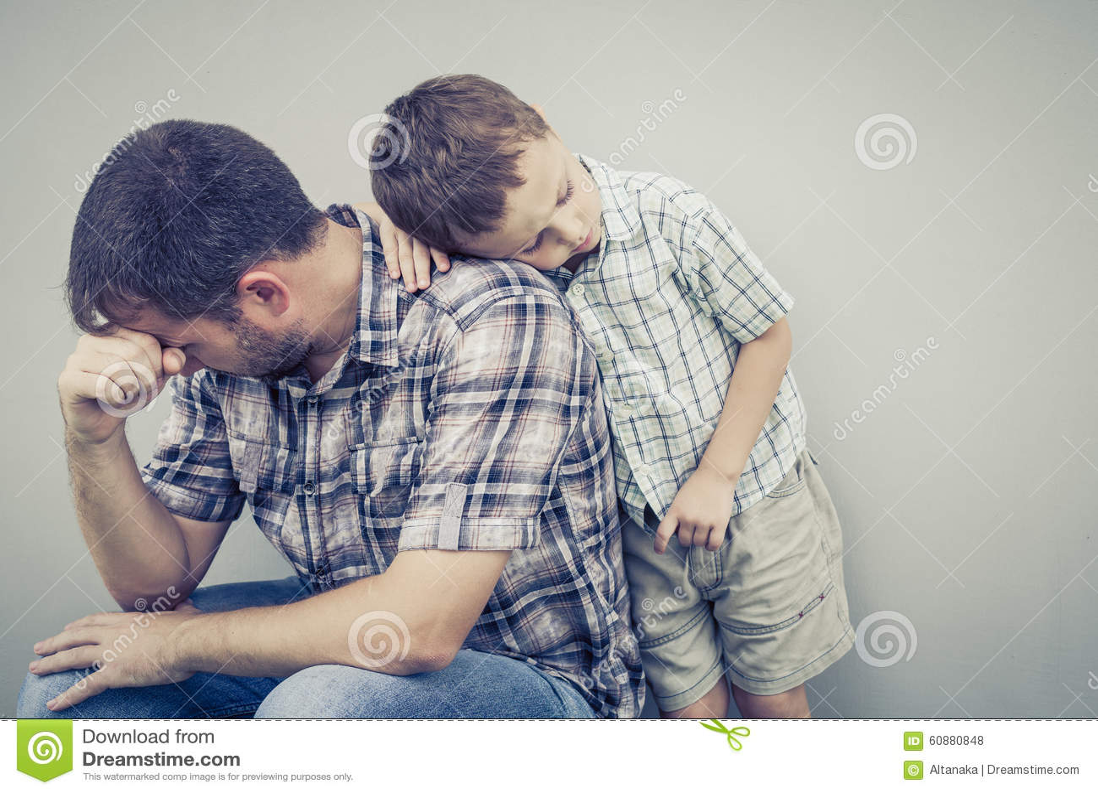 Trauriger Sohn, der seinen Vati nahe Wand umarmt