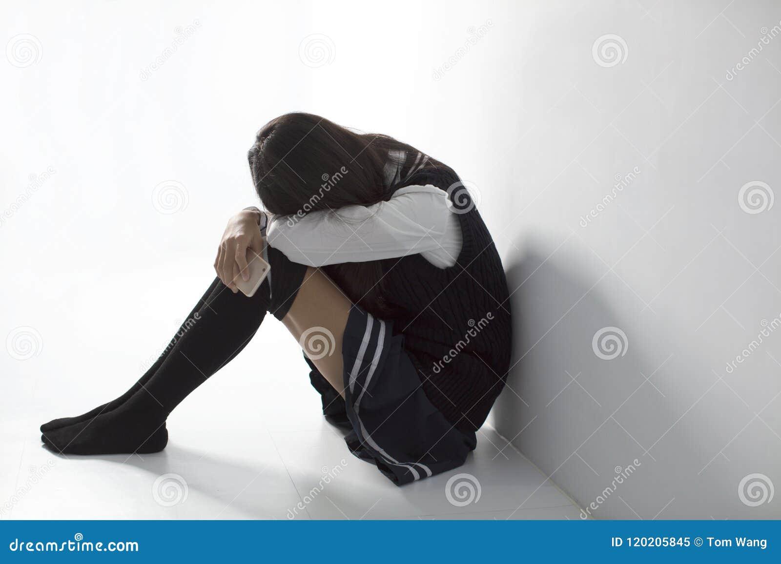 Trauriger Student, der Handy hält und auf dem flo sitzt