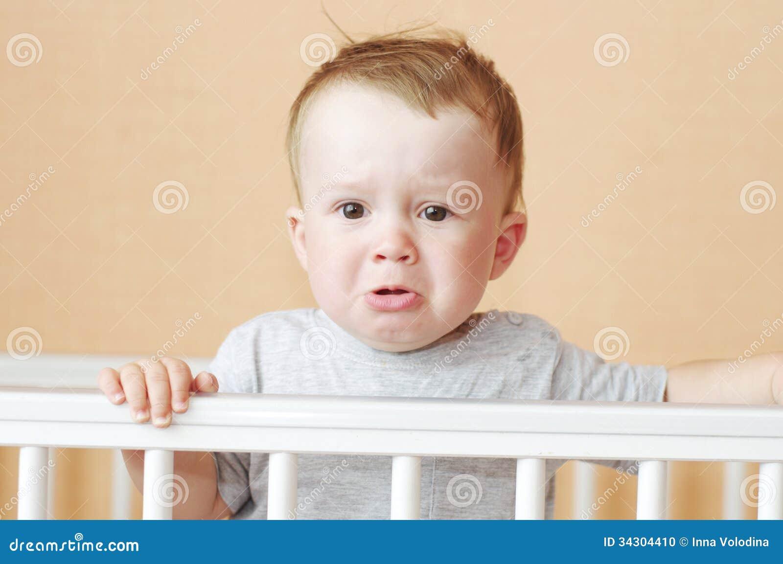 Trauriges Baby im weißen Bett