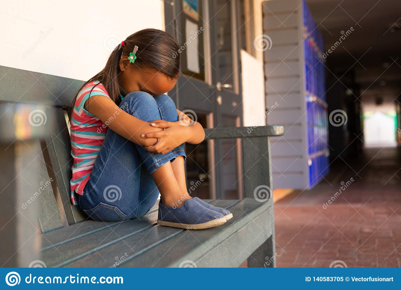 Trauriges Schulmädchen, das allein auf der Bank im Korridor sitzt