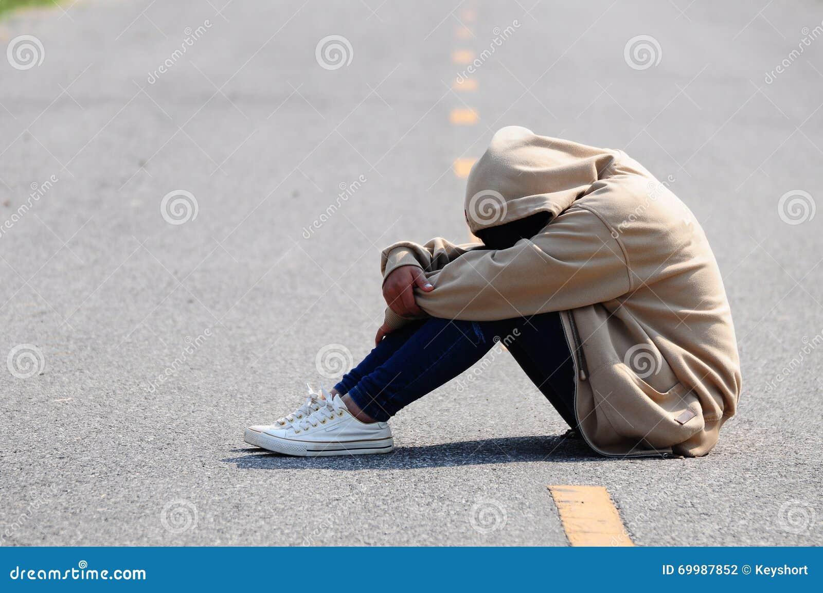Trauriges und nervöses Mädchen, das auf der Straße sitzt