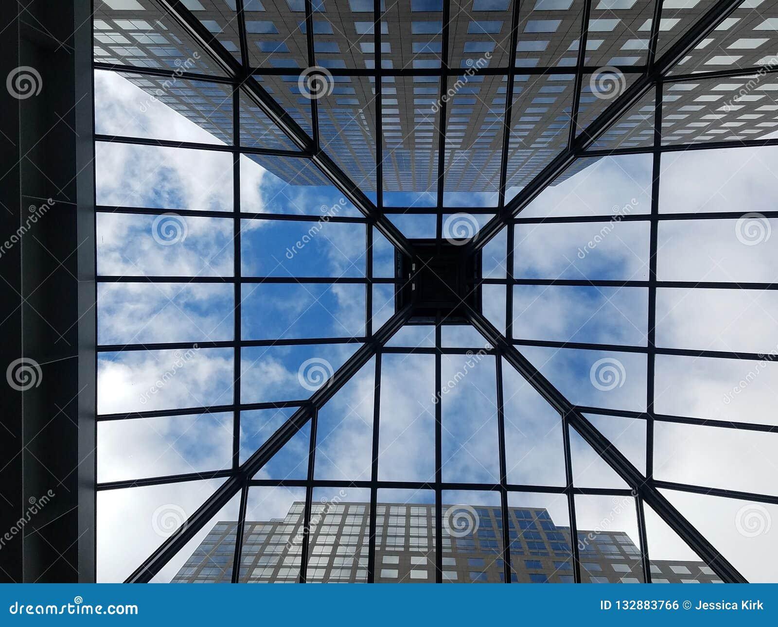 A través del tejado, mirando derecho encima a través del tejado de cristal del atrio los rascacielos