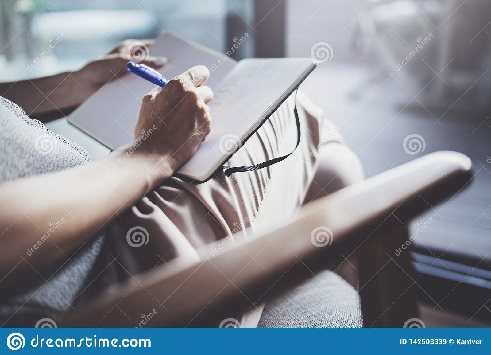 Travail à domicile de concept Jeunes écriture de femme d affaires et notes de prise tandis que détendez la séance dans la chaise