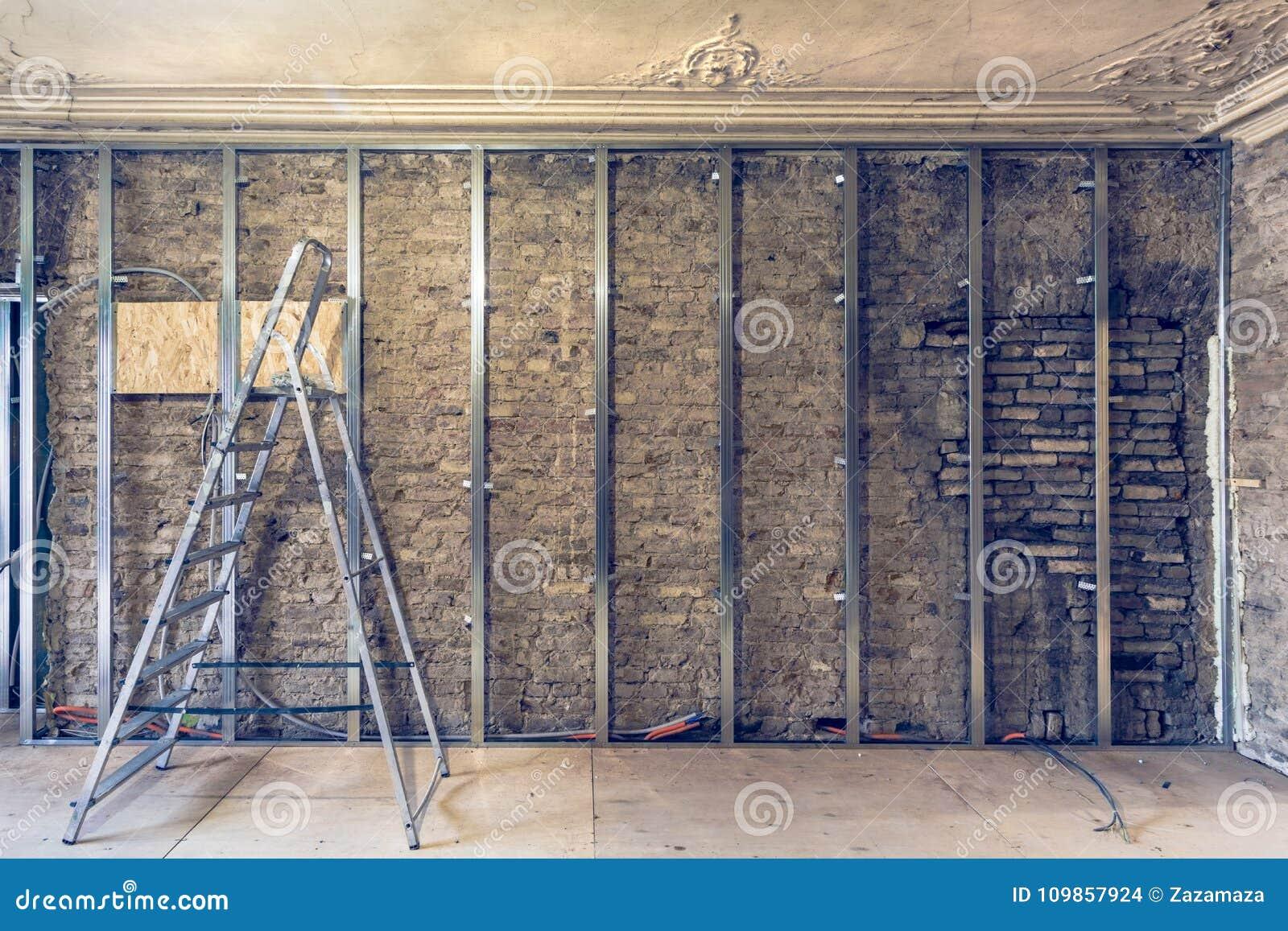 Travail de processus d installer des cadres en métal pour la cloison sèche de plaque de plâtre pour faire des murs de gypse avec