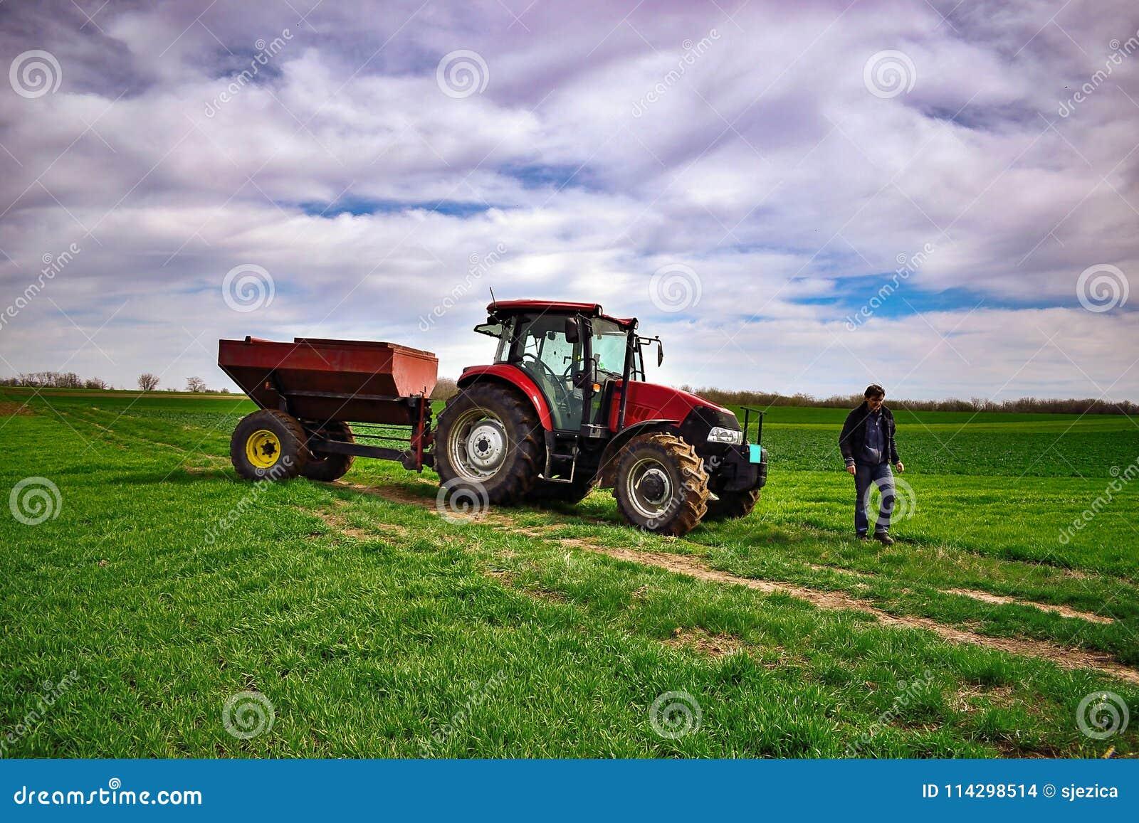 Travail de tracteur sur le champ Appliquant l engrais au printemps