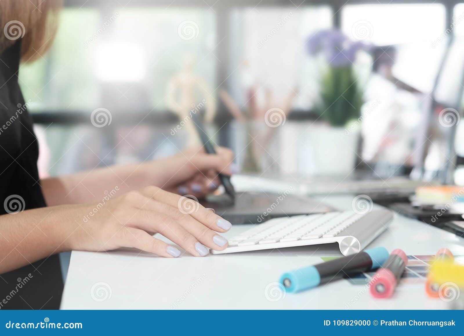 Travailler créatif de femme de conception graphique à la table avec le stylo de souris