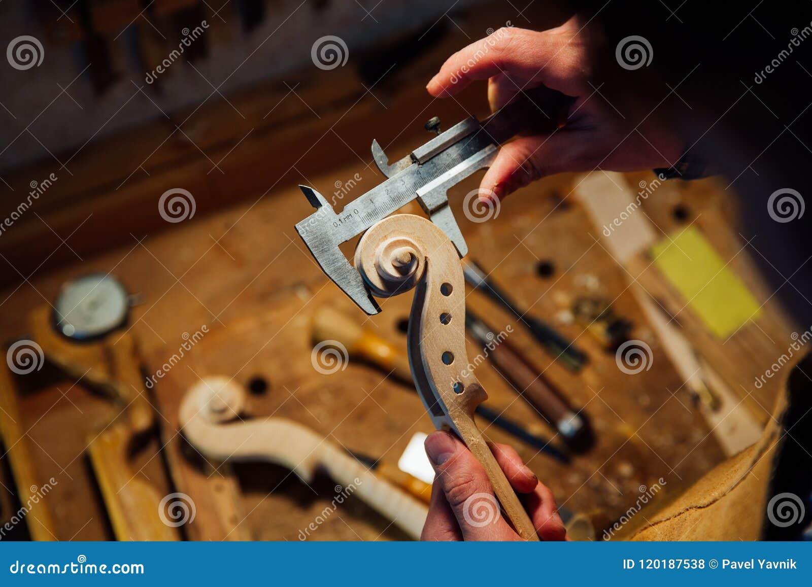 Travailler luthier d artisan principal à la création d un rouleau de violon travail détaillé sur le bois avec des outils