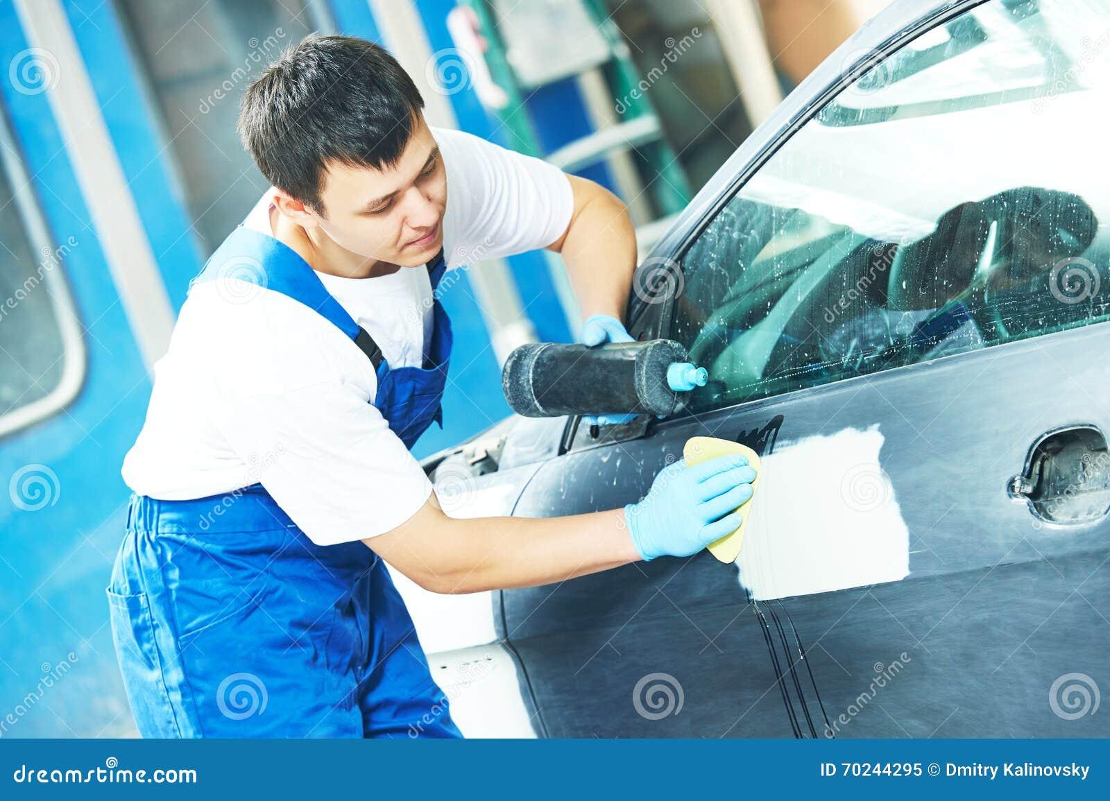 Travailleur appliquant le poli de voiture