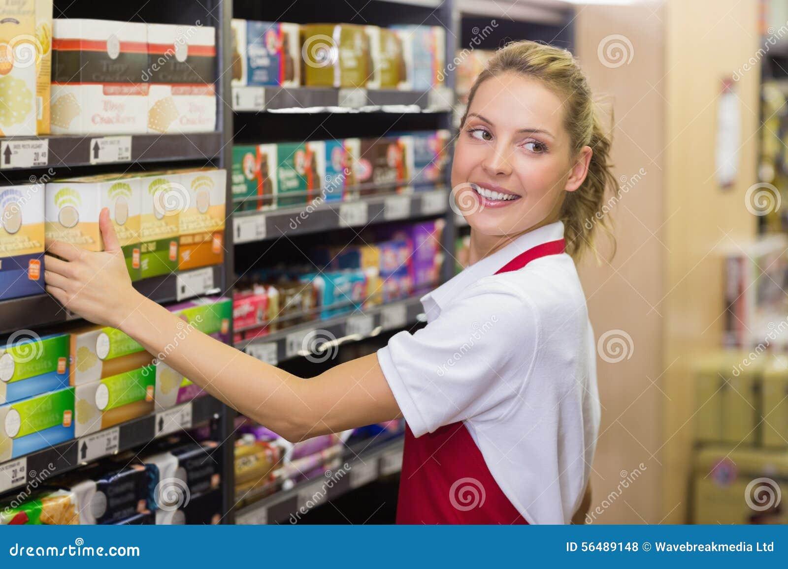 Travailleur blond de sourire prenant un produit dans l étagère