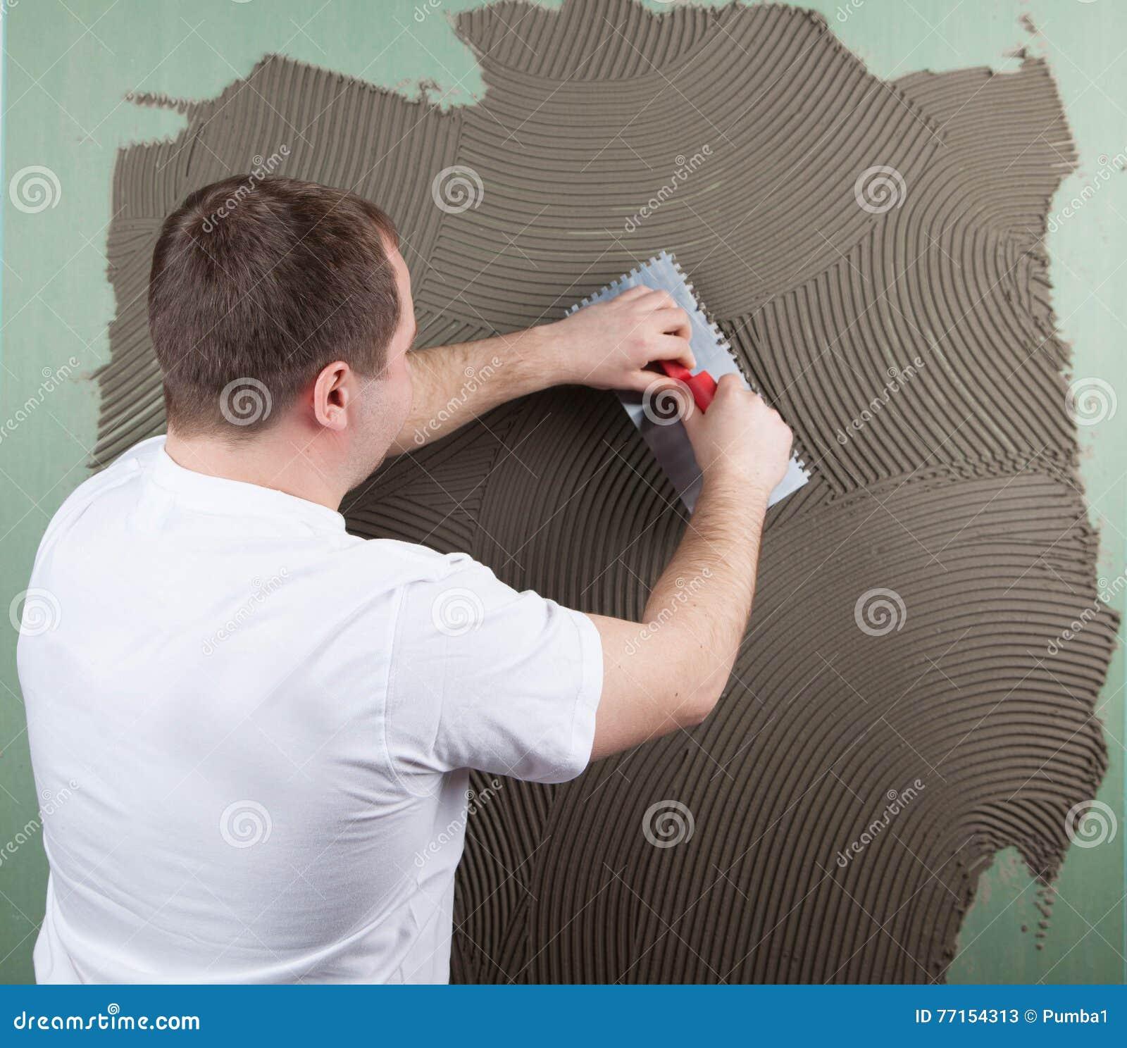 Travailleur de constructeur au mur de la construction de maison