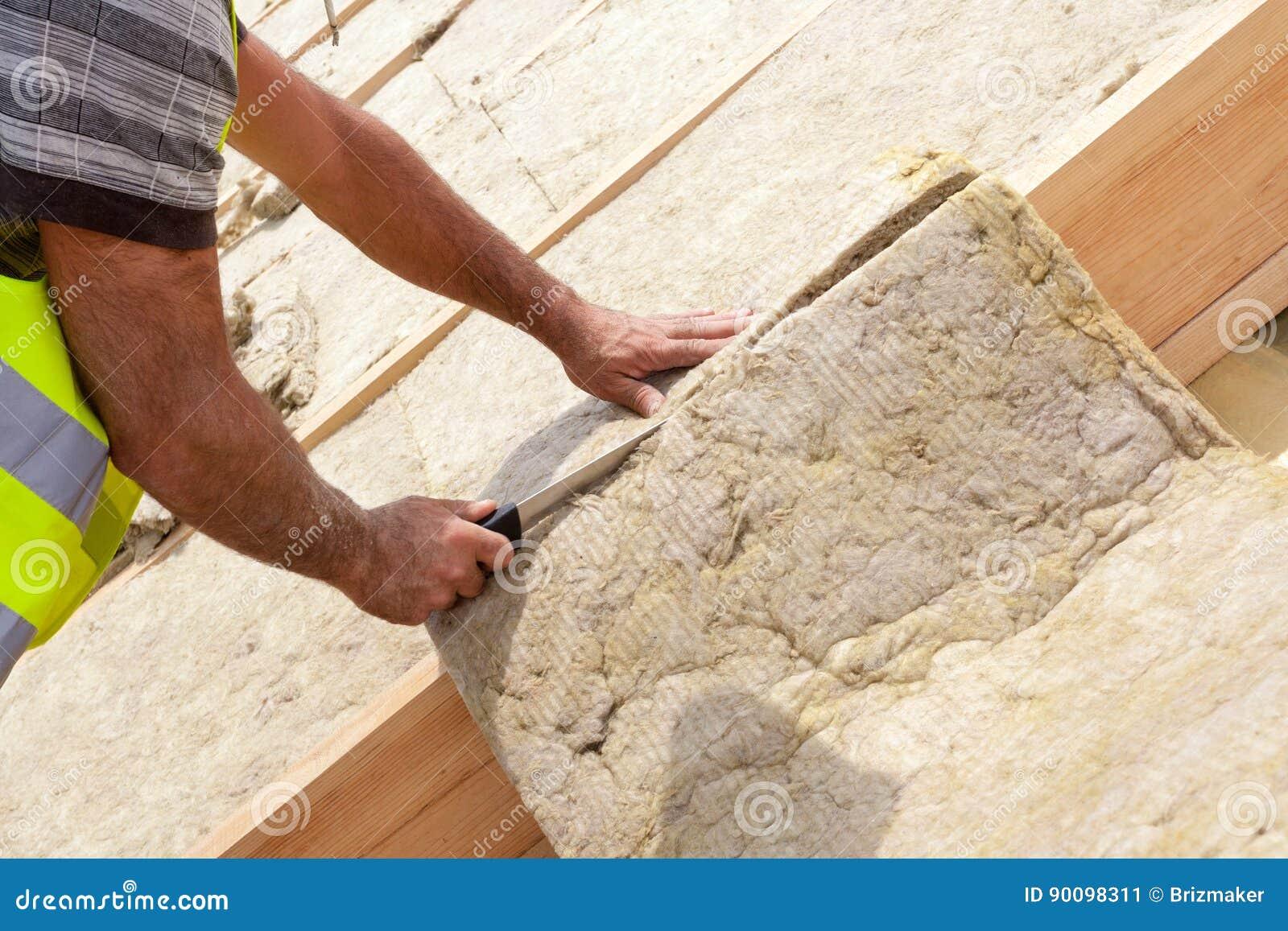 Travailleur de constructeur de Roofer installant le matériel d isolation de toit sur la nouvelle maison en construction Rockwall