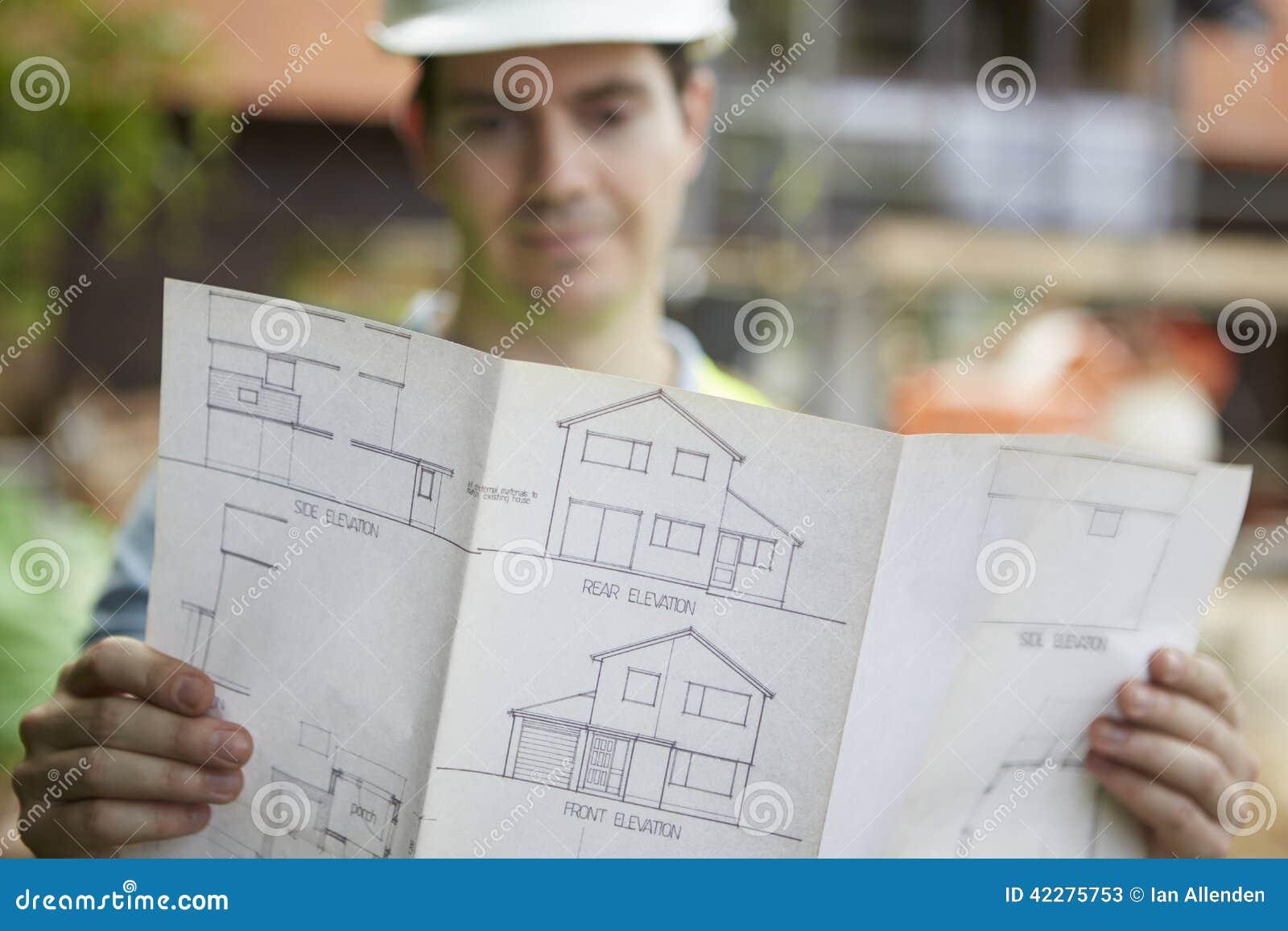 Travailleur de la construction On Building Site regardant des plans de Chambre