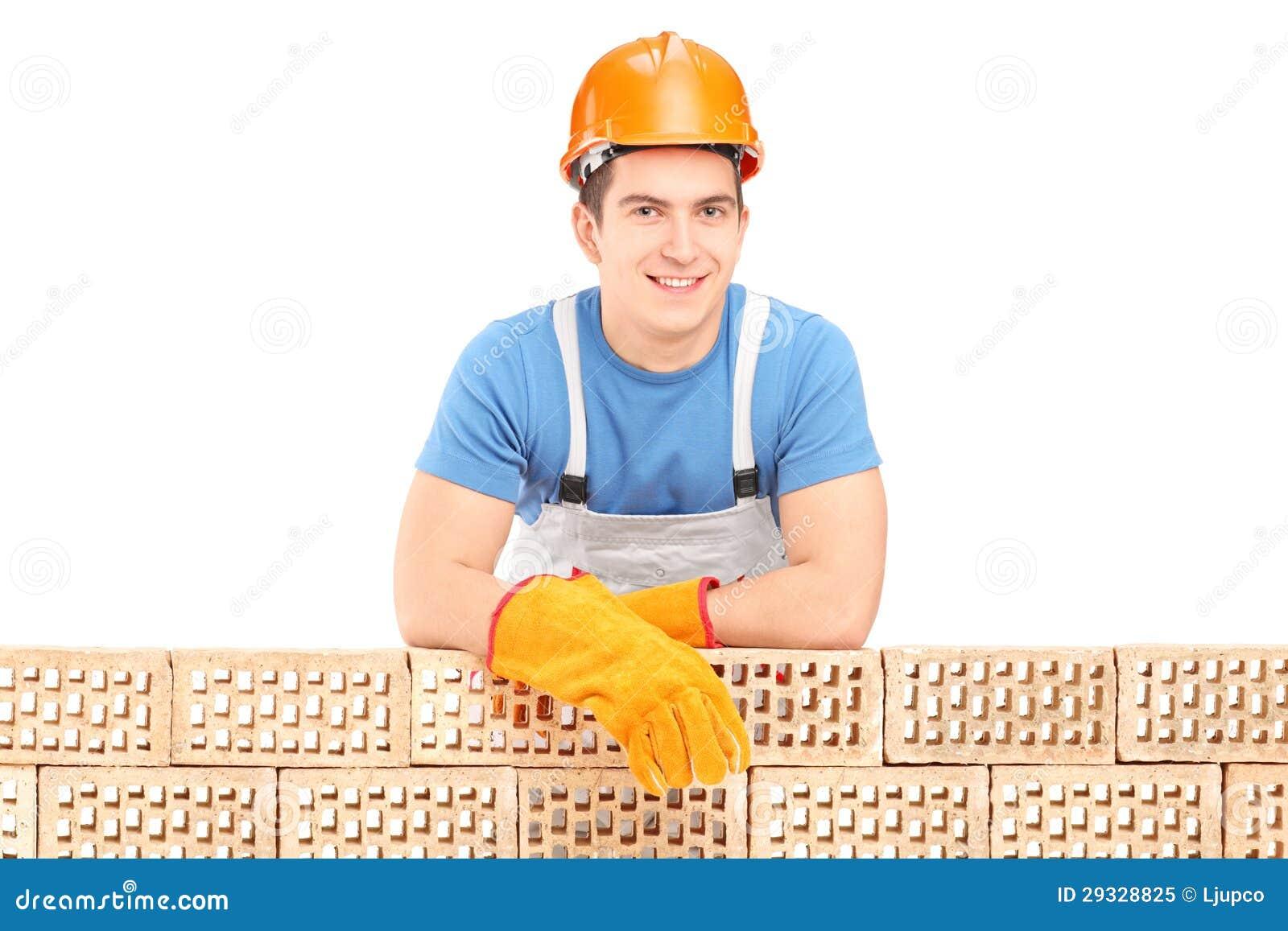 Travailleur de la construction de sexe masculin se reposant sur un mur de briques