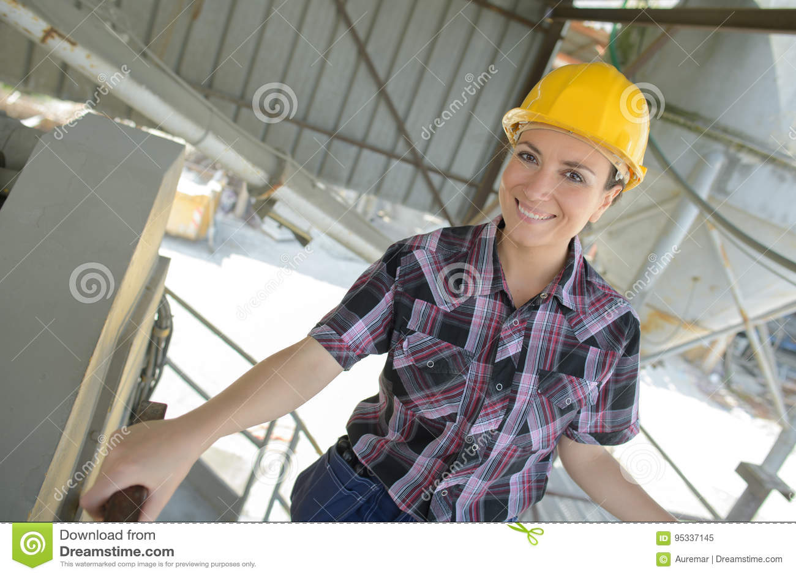 Travailleur de la construction féminin de sourire de portrait de plan rapproché au site