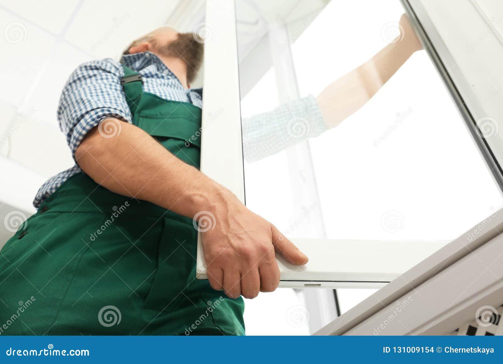 Travailleur de la construction installant la nouvelle fenêtre