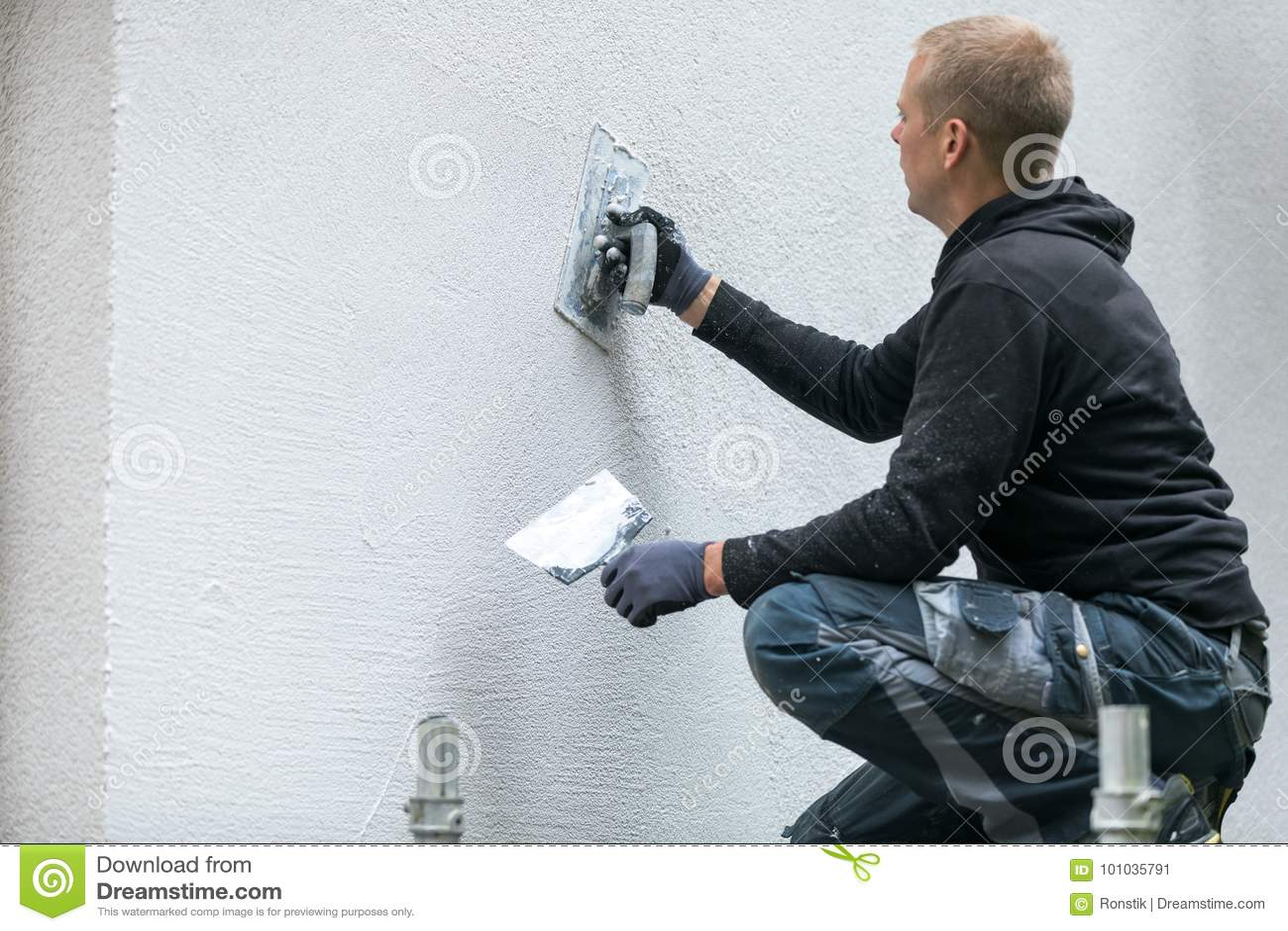 Travailleur de la construction mettant le plâtre décoratif sur l extérieur de maison