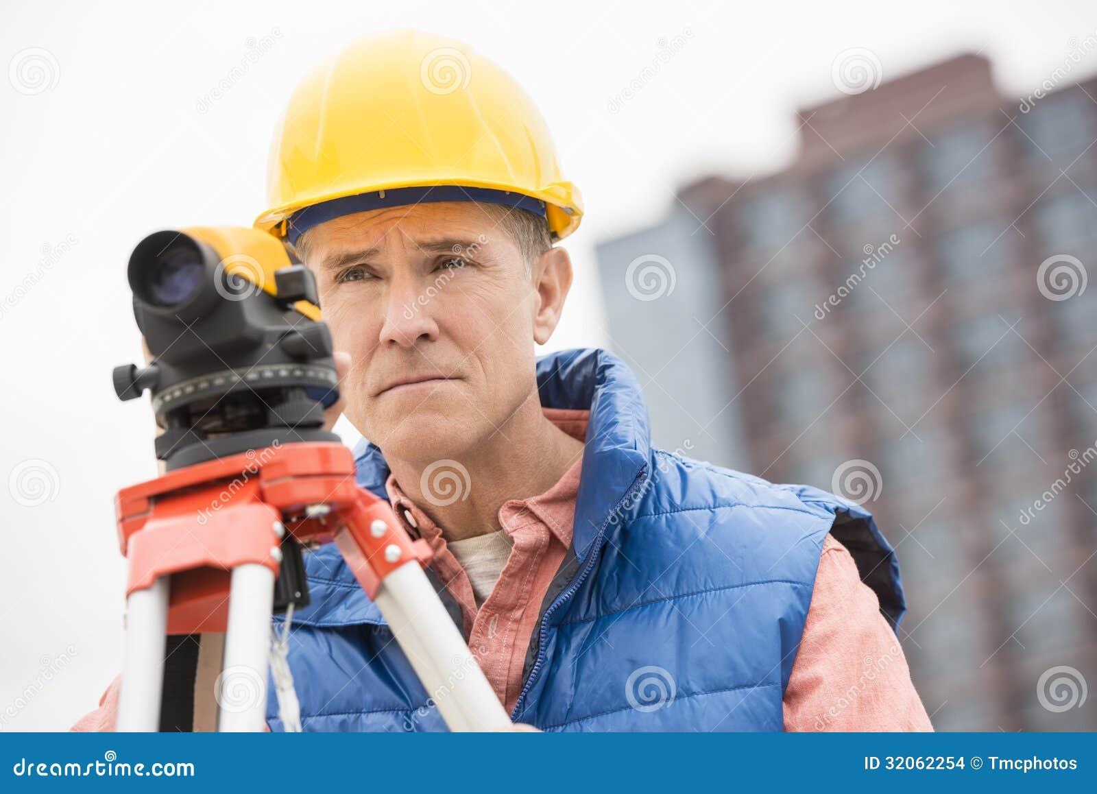 Travailleur de la construction sûr With Theodolite Looking loin