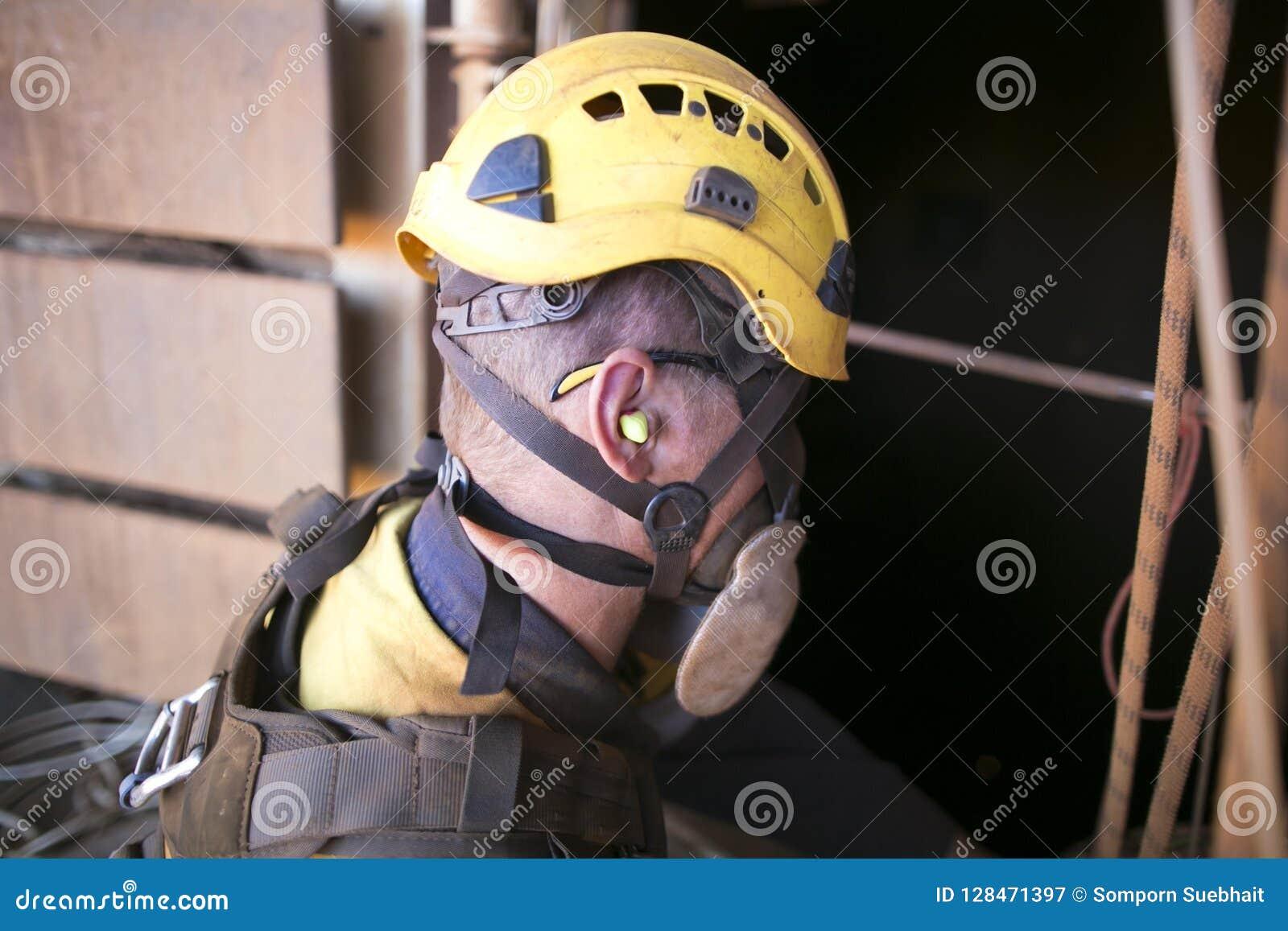 Travailleur de mineur portant une protection de sécurité de bruit de prise d oreille en travaillant près des machines d usine de