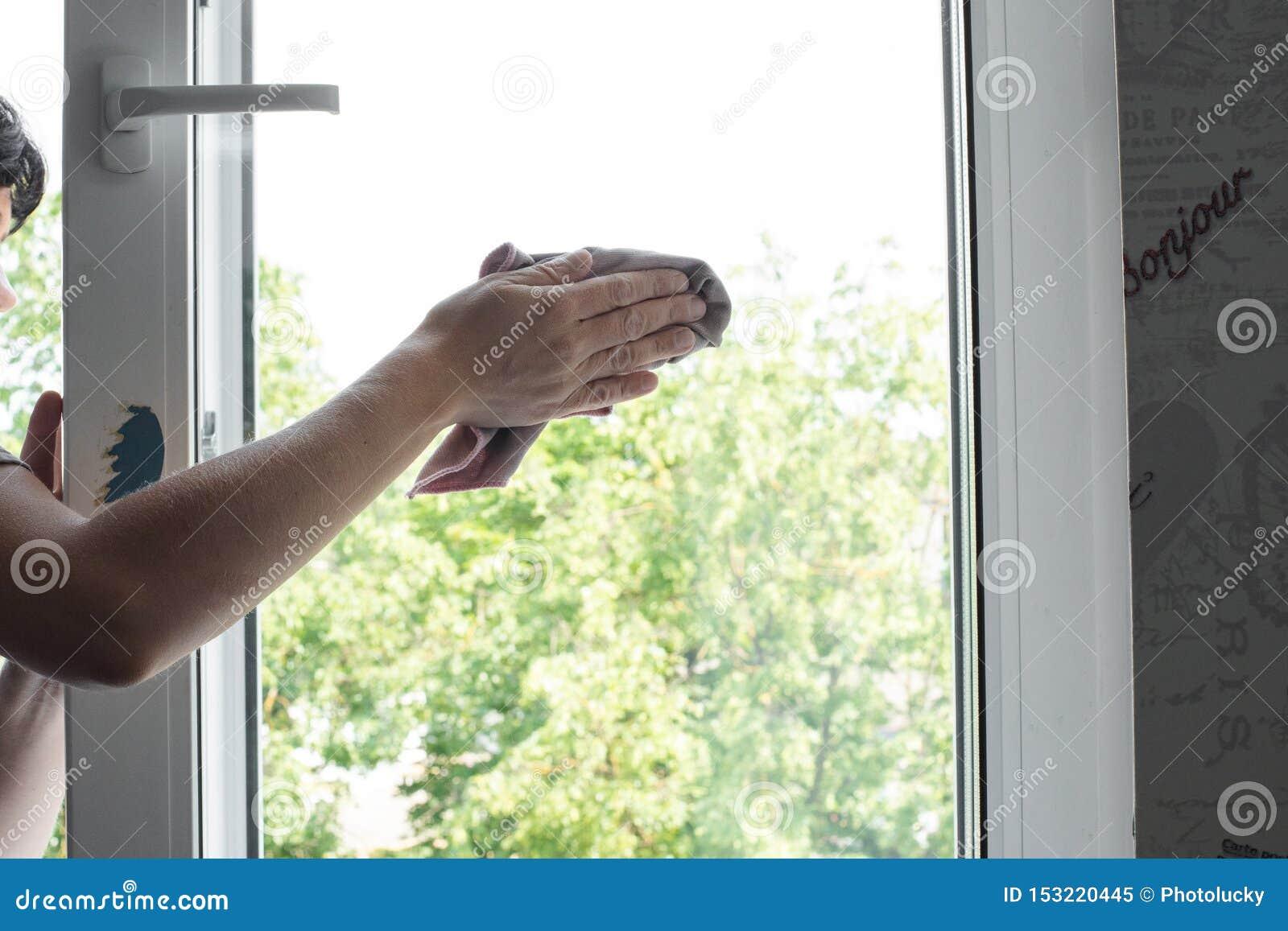 Travailleur de sexe masculin gardant le chiffon à disposition et essuyant la fenêtre