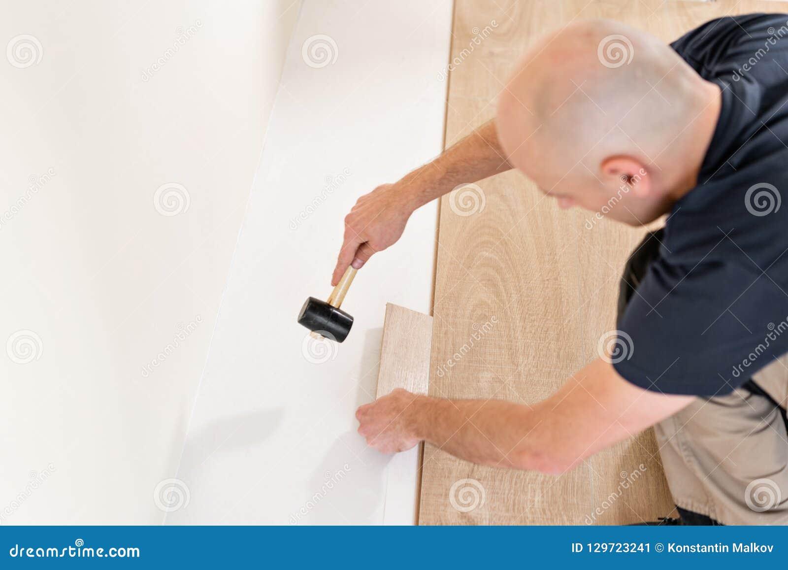 Travailleur de sexe masculin installant le nouveau plancher en stratifié en bois sur un plancher chaud d aluminium de film systèm