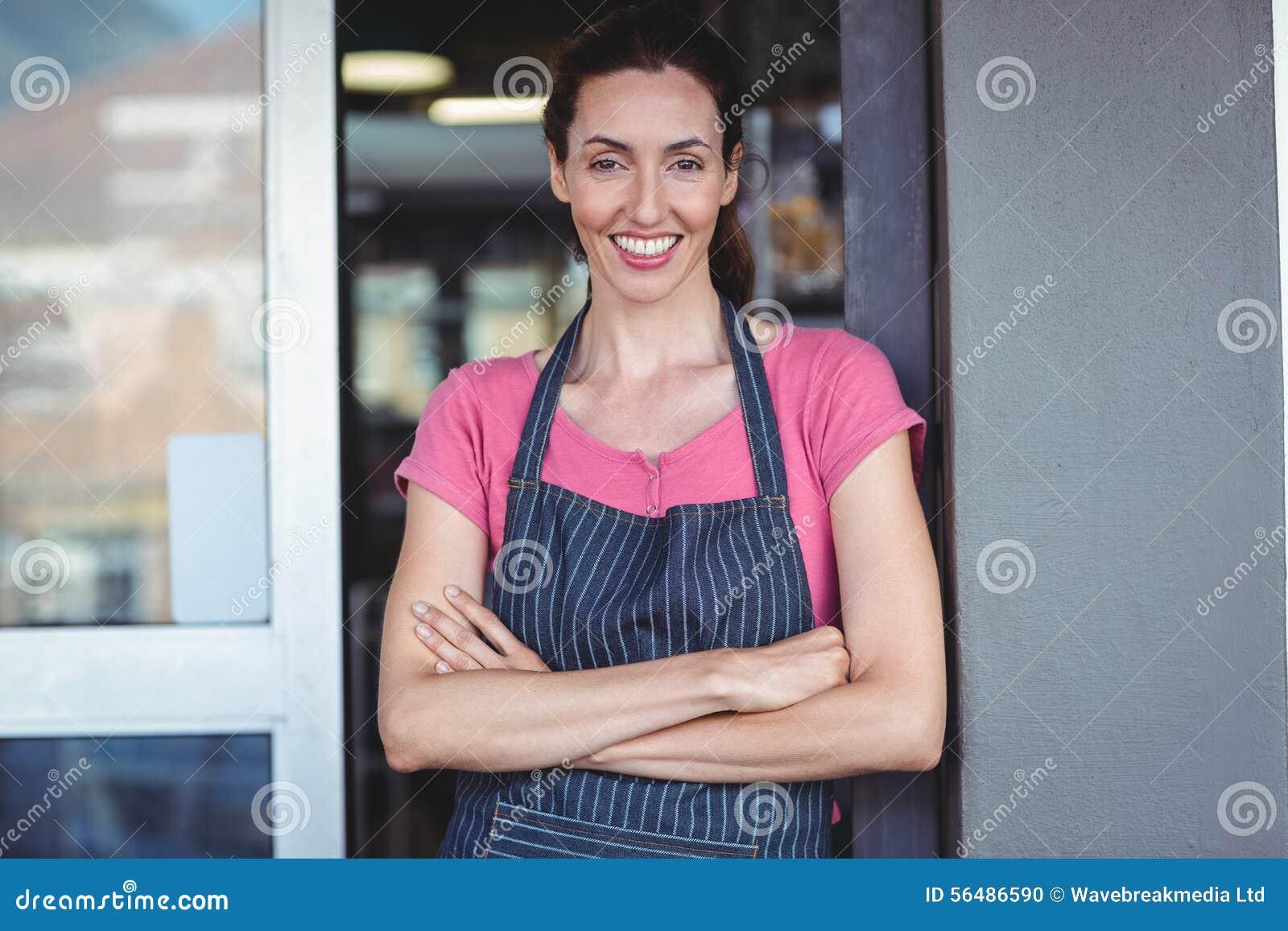 Travailleur de sourire regardant l appareil-photo avec le bras croisé