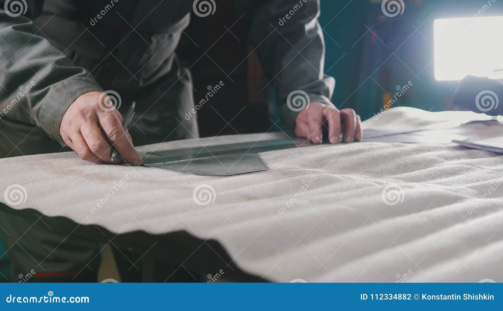 Travailleur faisant des mesures et des marques sur une pièce au moyen d une règle