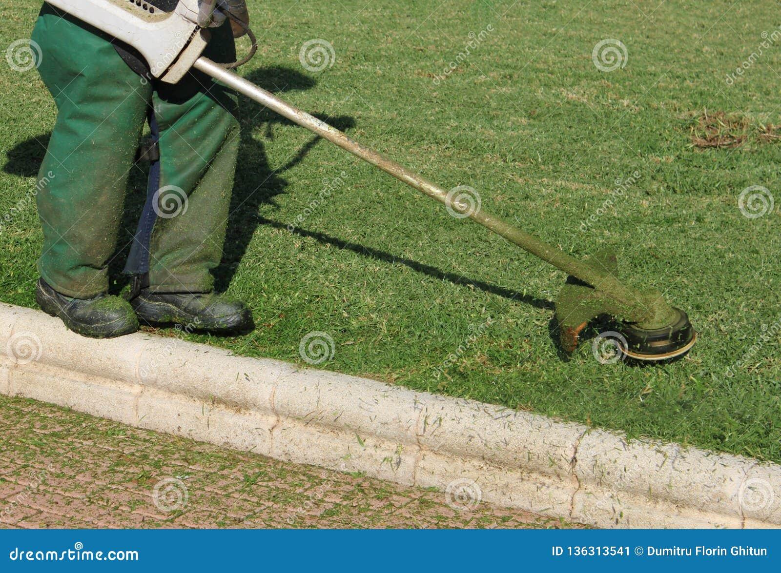 Travailleur fauchant les pelouses