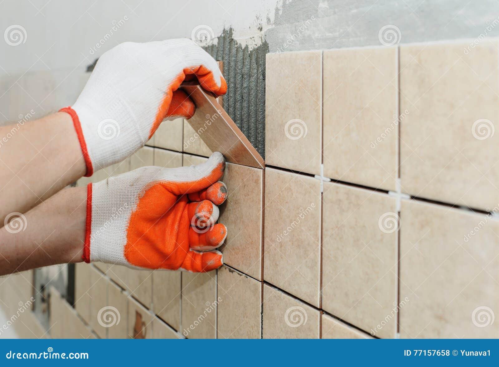 Travailleur mettant des tuiles sur le mur dans la cuisine