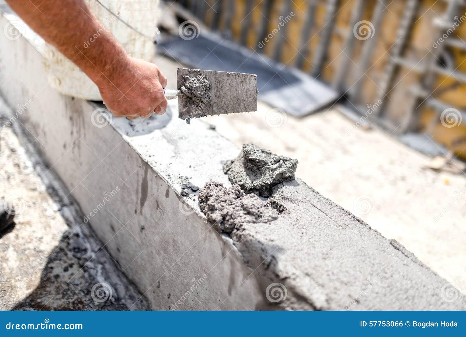 Travailleur nivelant le béton avec le couteau de mastic au chantier Détails d industrie du bâtiment