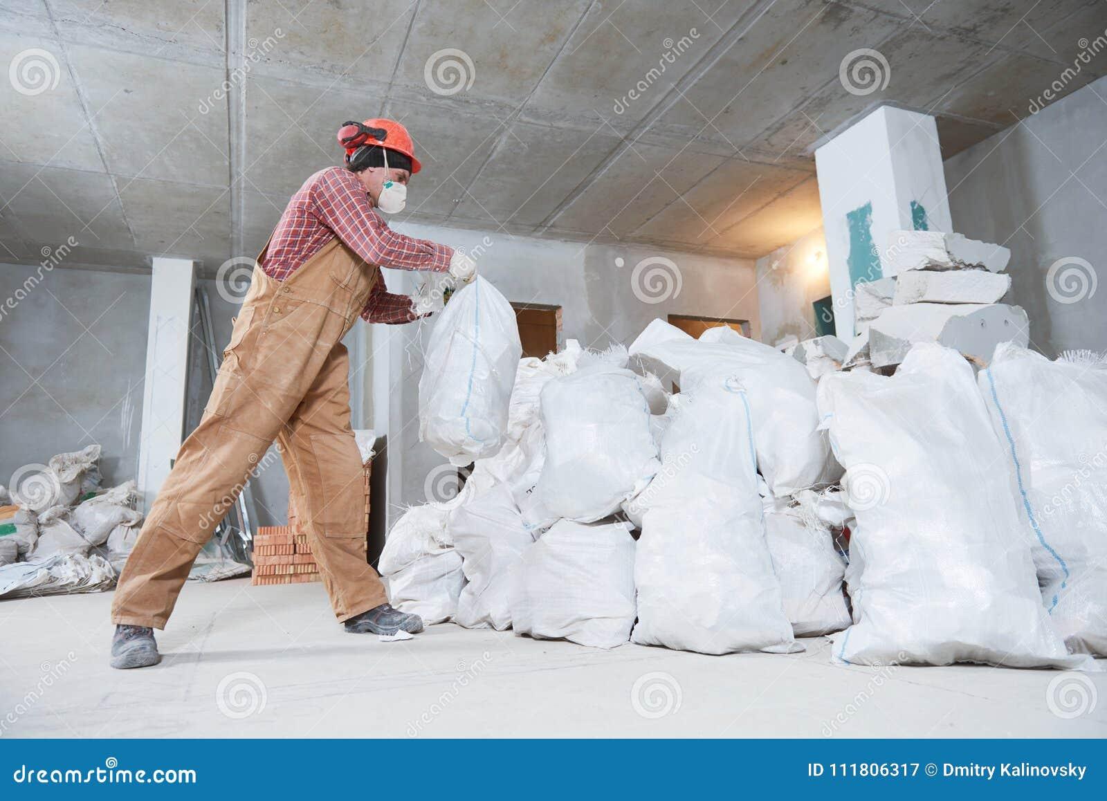 Travailleur rassemblant des déchets de construction dans le sac
