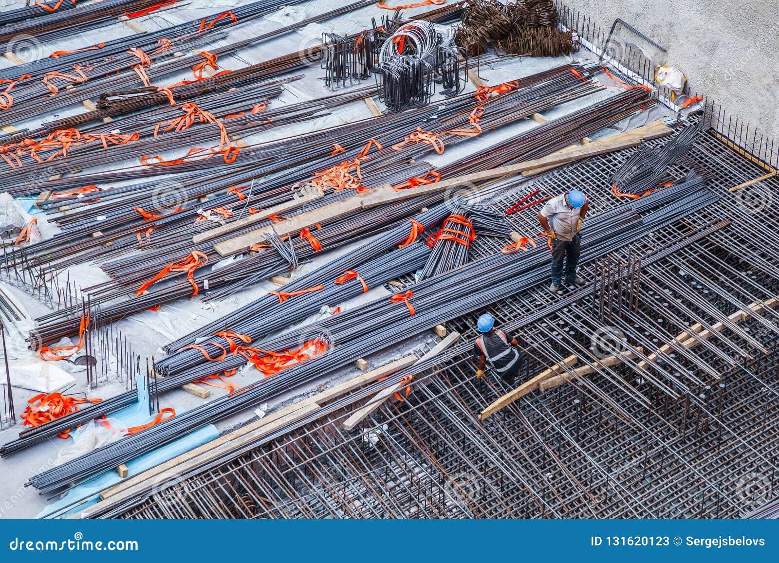Travailleurs de la construction fabriquant la barre en acier de renfort au chantier de construction