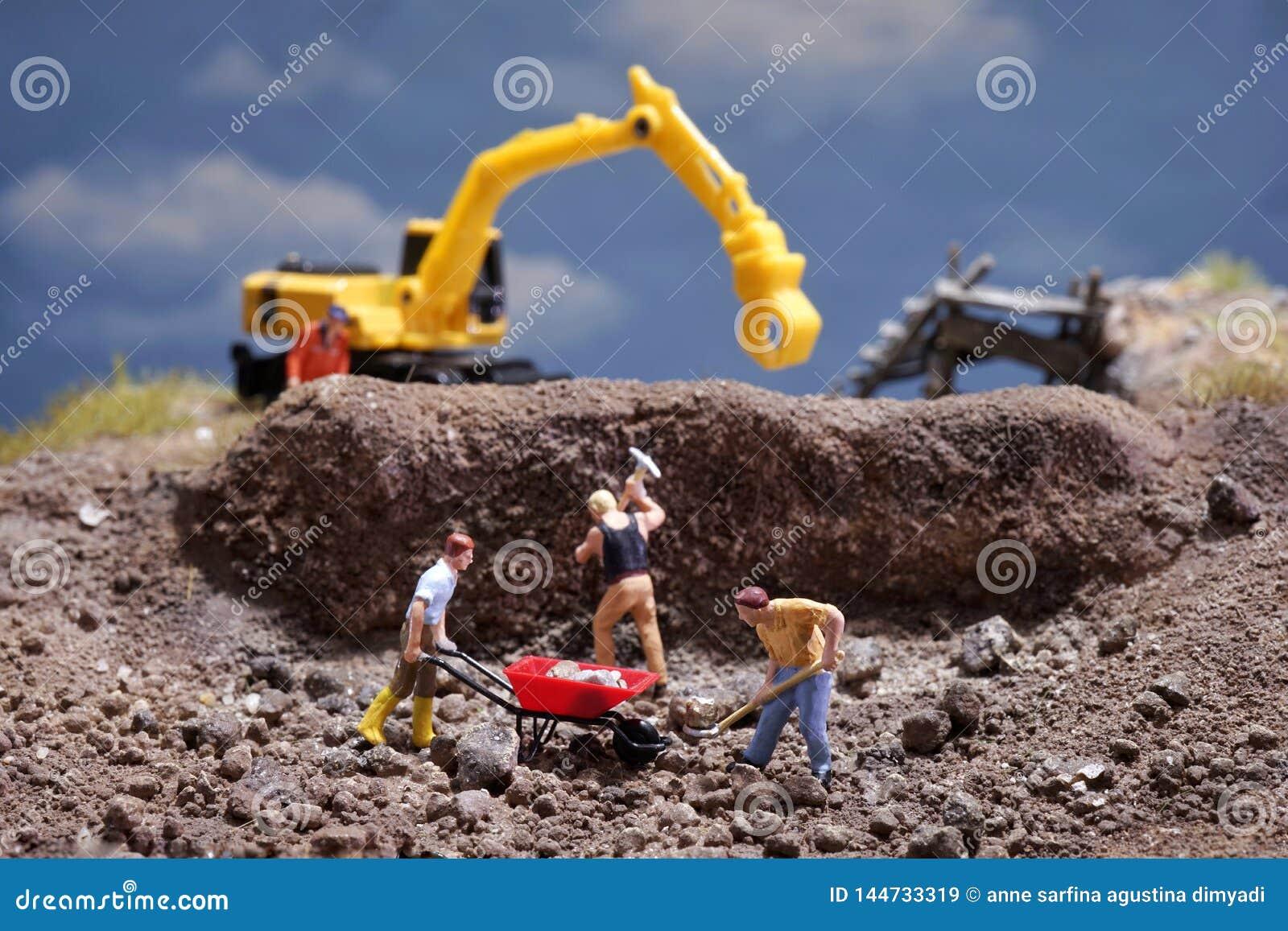 Travailleursde MiniatureContruction travaillant la pierre de levage utilisant la pelle