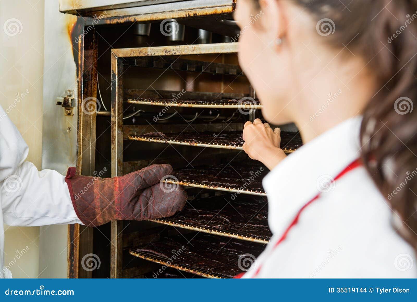 Travailleurs enlevant les tranches sèches de viande d Oven At