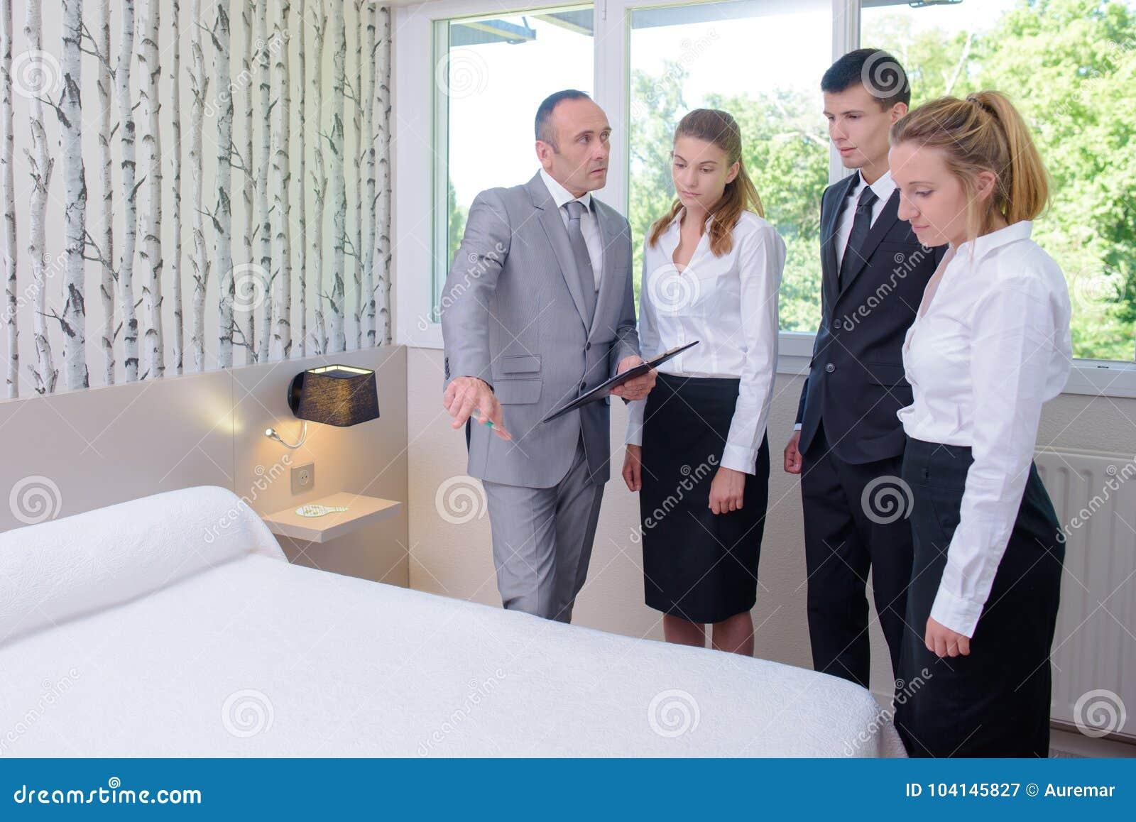 Travailleurs et directeur de ménage de service hôtelier dans la chambre d hôtel