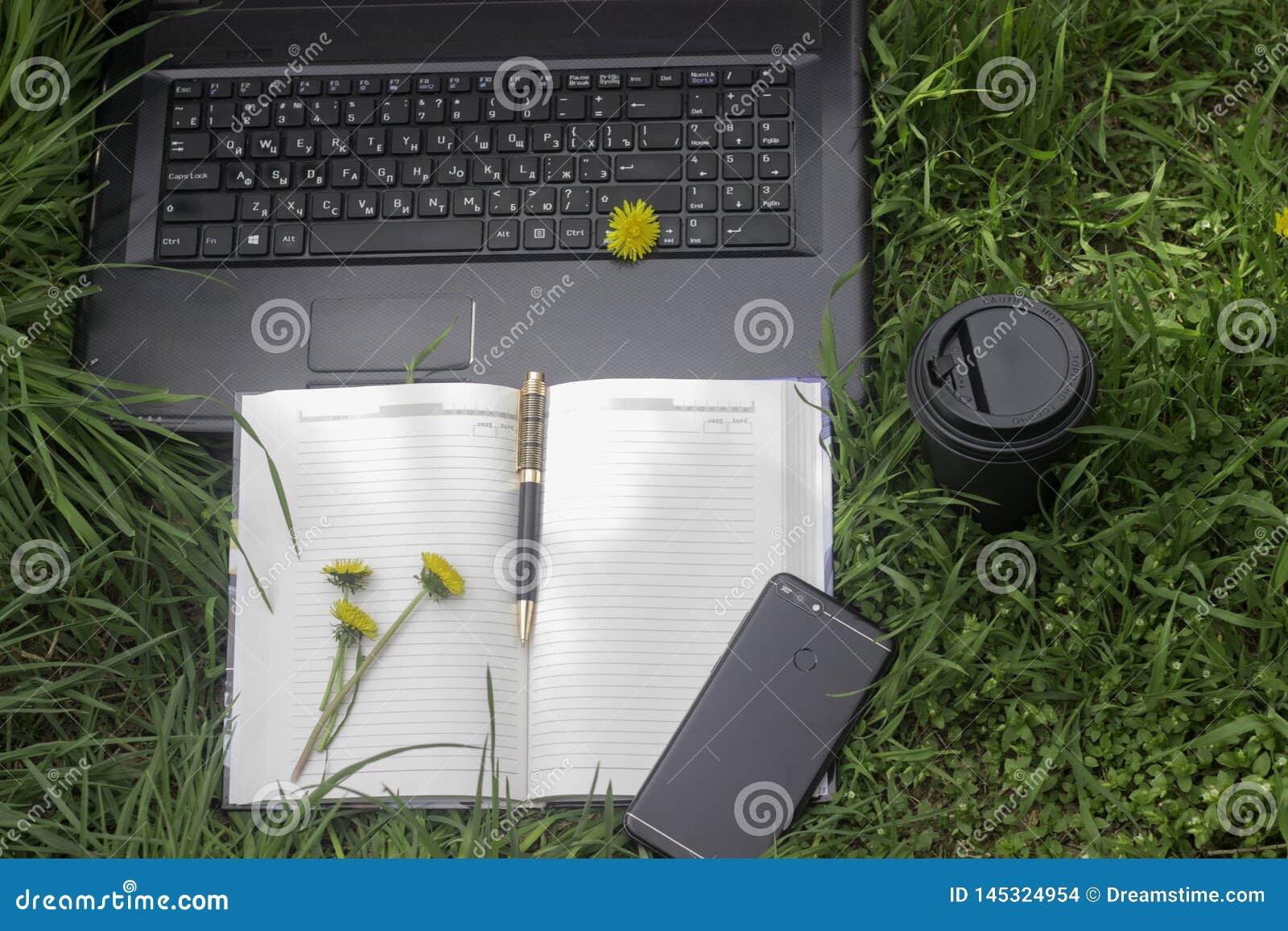 Travaillez dehors avec le téléphone, l ordinateur portable et le coffe