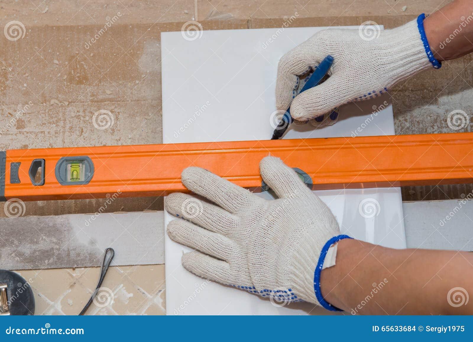 Travaux de construction étendant la tuile sur le mur