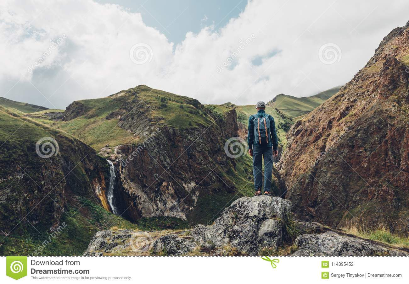 Travel Adventure Concept. Hiking Man Standing On Top Of Cliff In Mountains And Enjoying View Of Nature, Rear View