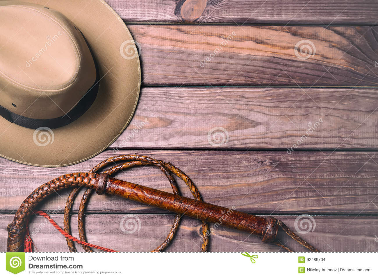 Travel and adventure concept. Vintage fedora hat and bullwhip on wooden table. Top view