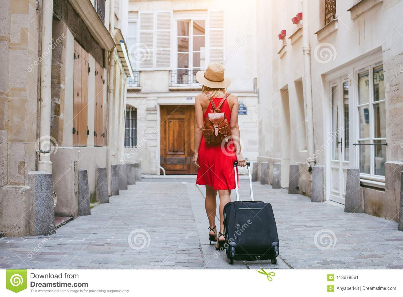 Travel background, woman tourist walking with suitcase on the street in european city, tourism