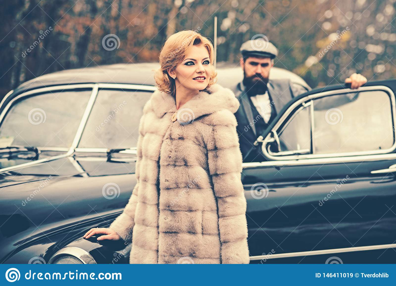 Travel and business trip or hitch hiking. Bearded man and sexy woman in fur coat. Retro collection car and auto repair