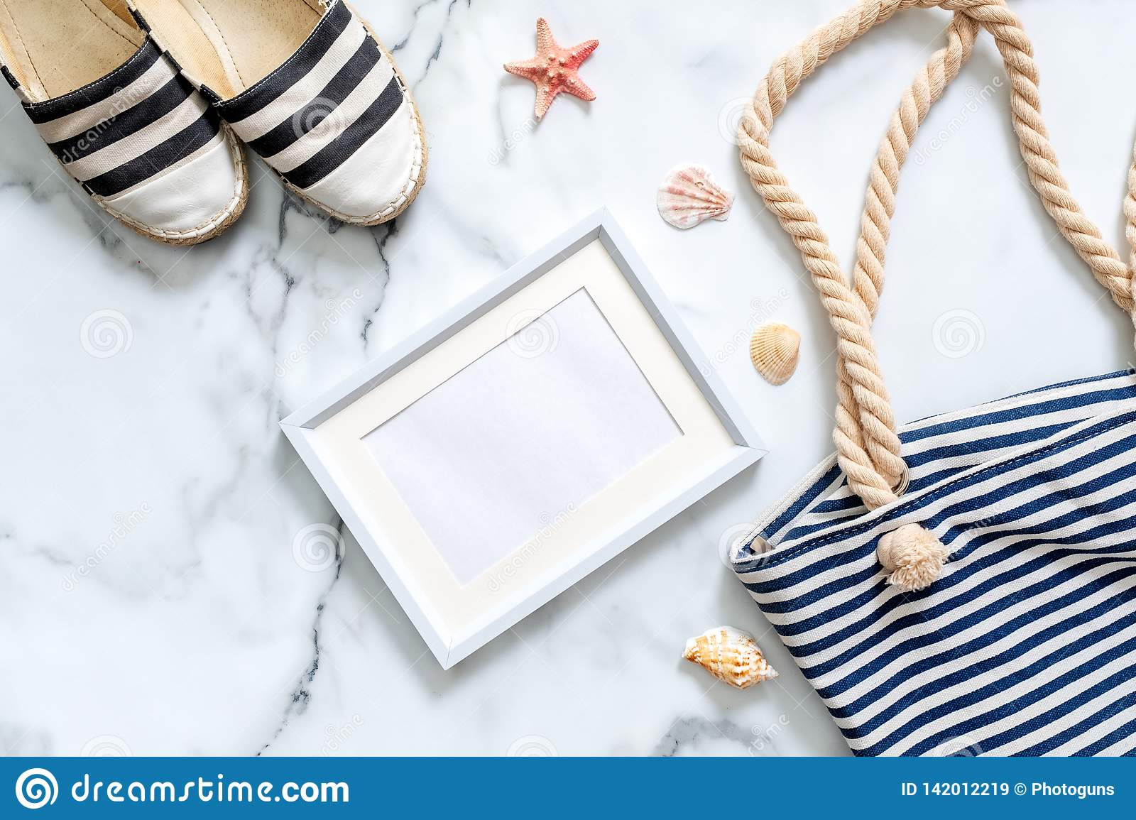 Travel composition on a marble background. Women`s desk with striped sandals, beach bag, seashells and blank picture frame. Lifes