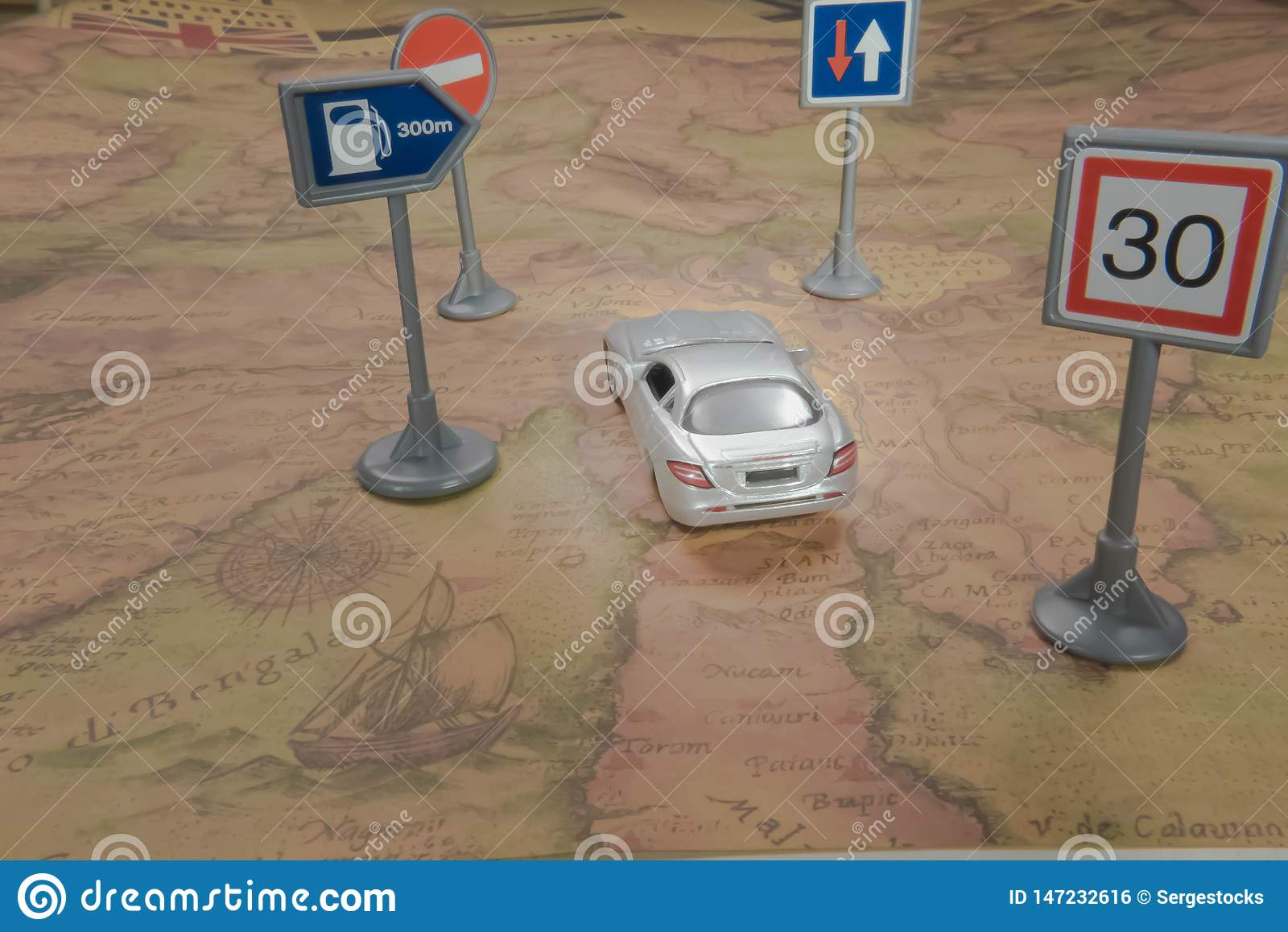 Travel concept. Toy car on vintage World map with road sign