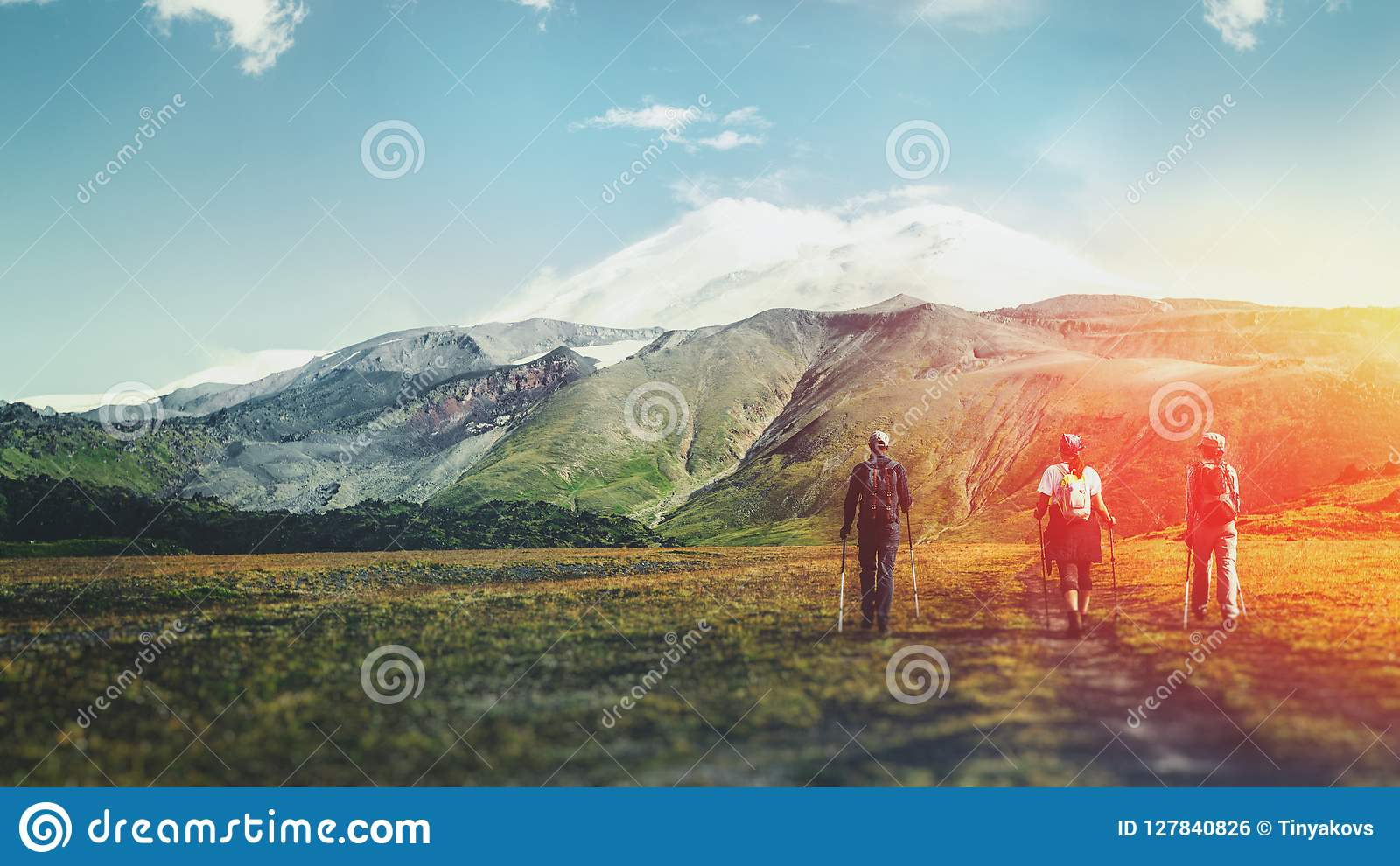 Travel Destination Experience Lifestyle Concept concept. Team of travelers with backpacks and trekking sticks climbs the mountain