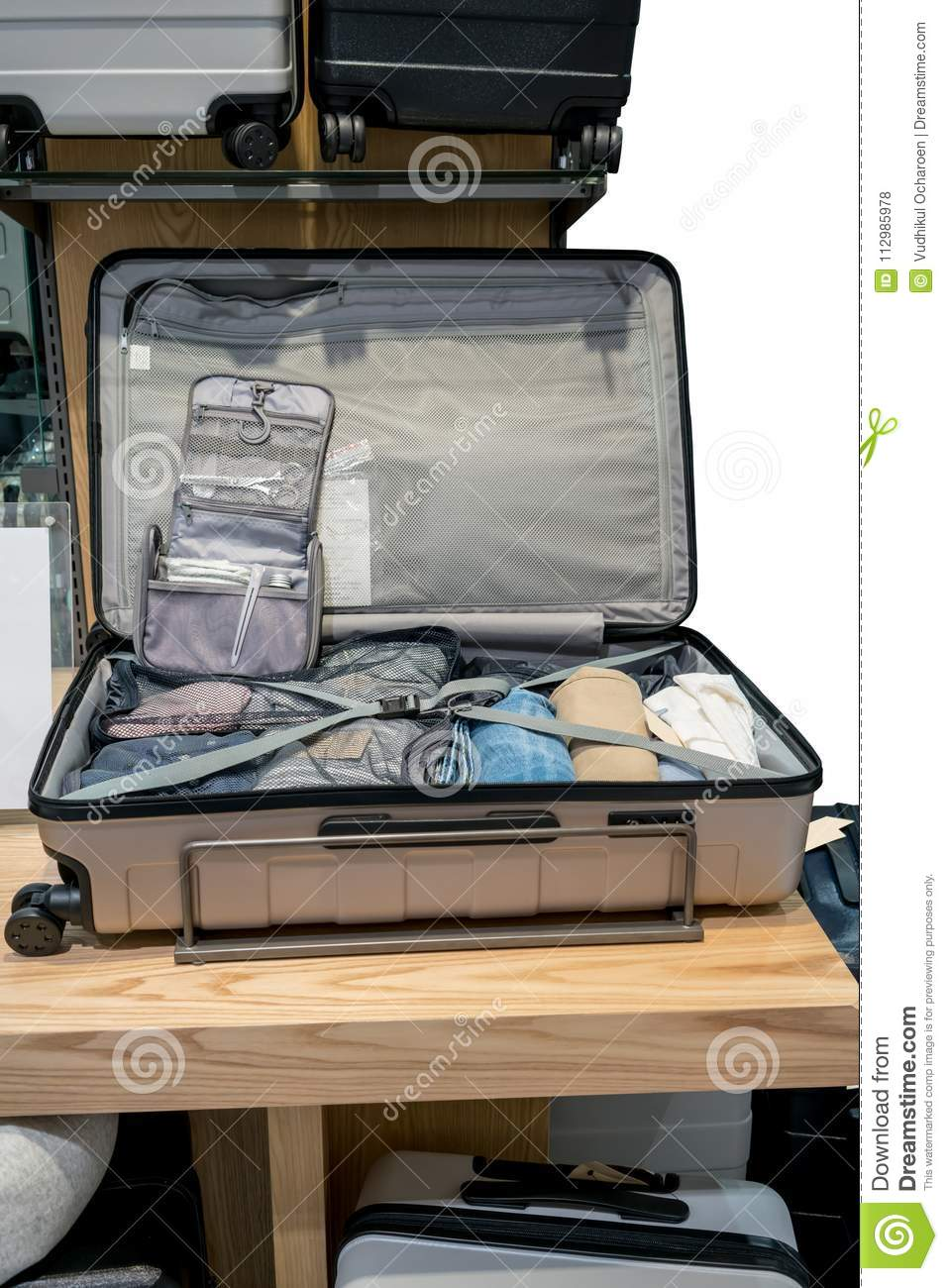 Travel smart packing in luggage on wooden table. Professional suitcase organization