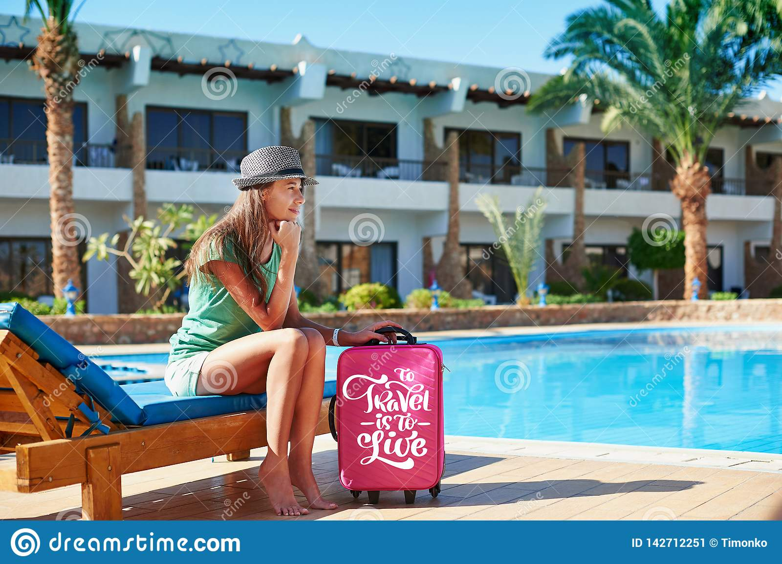 Travel, summer holidays and vacation concept - Beautiful woman walking near hotel pool area with red suitcase in Egypt