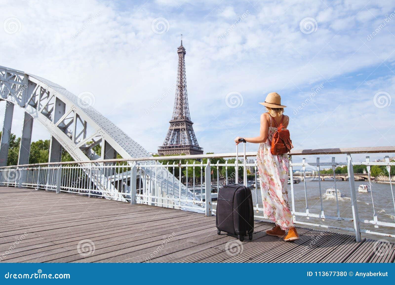 Travel to Paris, Europe tour, woman with suitcase near Eiffel Tower