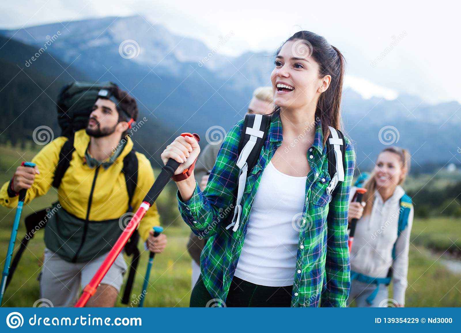 Travel, tourism, hike, gesture and people concept - group of smiling friends with backpacks